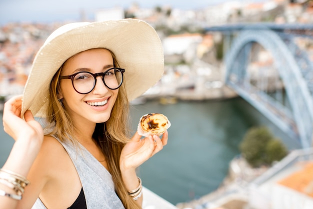 Porträt einer jungen frau, die ein traditionelles portugiesisches dessert namens pastel de nata genießt und auf der terrasse mit schönem blick auf das stadtbild auf porto, portugal sitzt