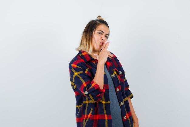 Porträt einer jungen frau, die eine pistolengeste im karierten hemd zeigt und selbstbewusst aussieht