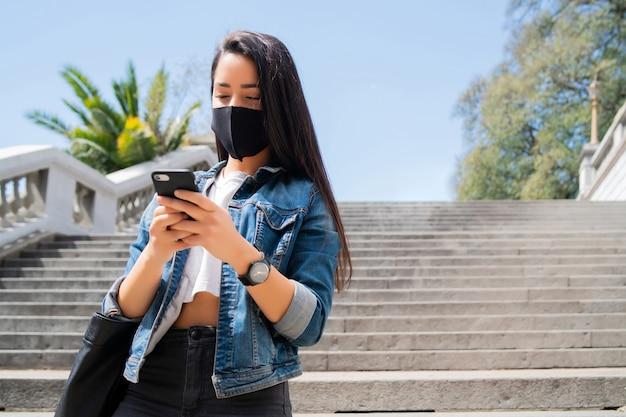 Porträt einer jungen frau, die eine schutzmaske trägt und ihr mobiltelefon benutzt, während sie im freien auf der straße steht. neues normales lifestyle-konzept. urbanes konzept.