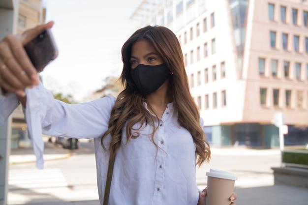 Porträt einer jungen frau, die eine schutzmaske trägt und mit ihrem mophilen telefon selfies macht, während sie im freien steht. urbanes konzept. neues normales lifestyle-konzept.