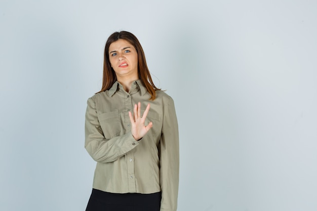 Porträt einer jungen frau, die eine stopp-geste zeigt, die stirn in hemd, rock und angewiderter vorderansicht runzelt