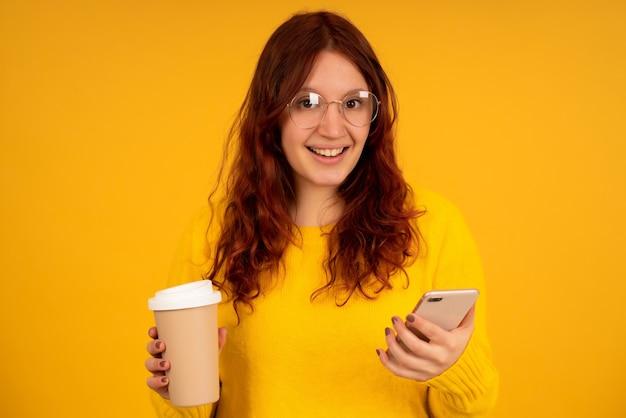 Porträt einer jungen frau, die eine tasse kaffee hält und ihr handy benutzt, während sie vor isoliertem hintergrund steht.