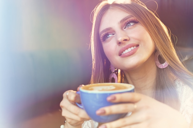Porträt einer jungen frau, die eine tasse kaffee trinkt und durch das fenster schaut