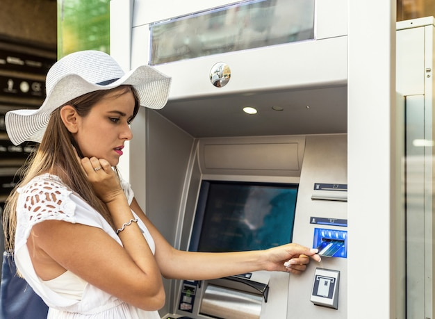 Porträt einer jungen frau, die einen atm-geldautomaten verwendet