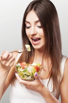Porträt einer jungen frau, die einen salat isst