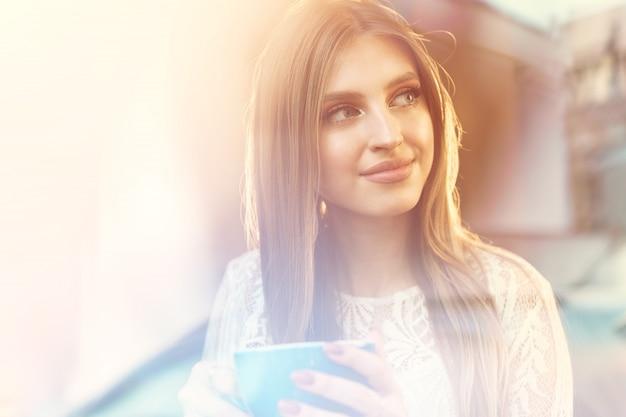 Porträt einer jungen frau, die einen tasse kaffee hat und durch das fenster schaut