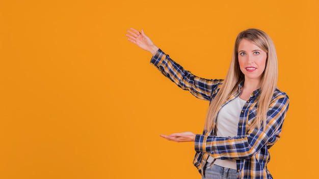 Porträt einer jungen frau, die etwas auf einem orange hintergrund darstellt