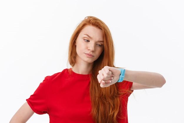 Porträt einer jungen frau, die finger auf armbanduhr zeigt, lokalisiert auf einem weiß