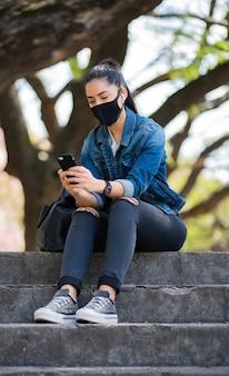 Porträt einer jungen frau, die gesichtsmaske trägt und ihr mobiltelefon benutzt, während sie im freien auf der treppe sitzt. neues normales lifestyle-konzept. urbanes konzept.