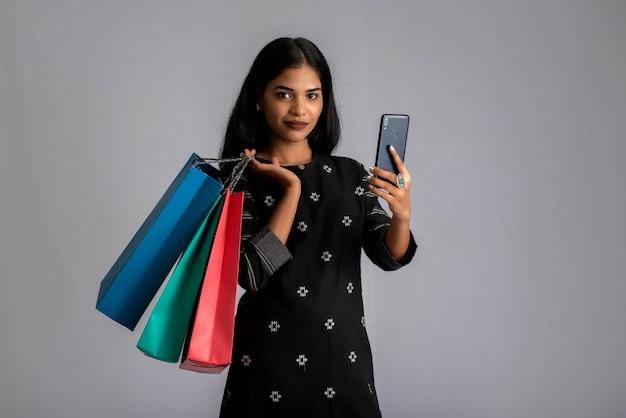 Porträt einer jungen frau, die handy mit einkaufstüten in ihren händen benutzt.