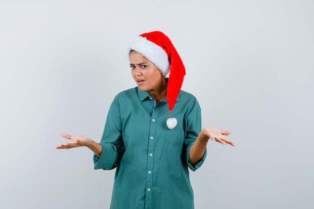Porträt einer jungen frau, die hilflose geste in hemd, weihnachtsmütze und zögerlicher vorderansicht zeigt