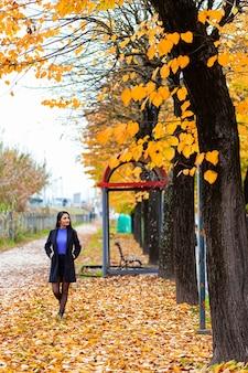 Porträt einer jungen frau, die im herbstpark geht