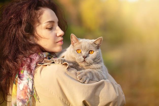 Porträt einer jungen frau, die im herbstpark mit einer katze im arm abends spaziert