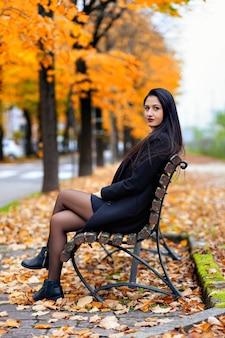 Porträt einer jungen frau, die im herbstpark sitzt