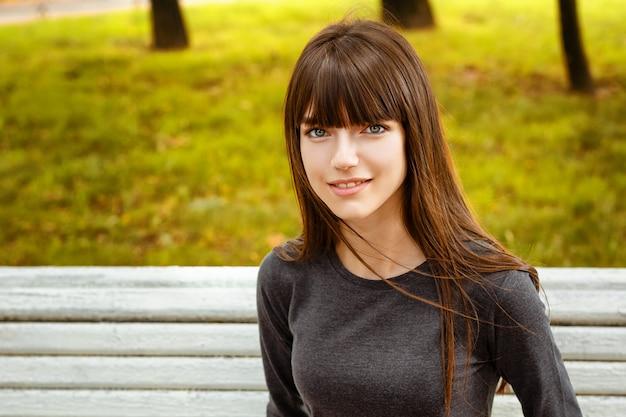 Porträt einer jungen frau, die im park auf einer bank sitzt