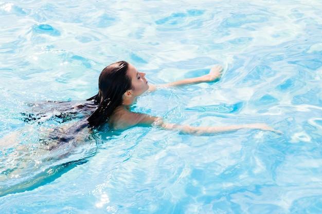 Porträt einer jungen frau, die im pool schwimmt
