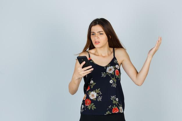 Porträt einer jungen frau, die in bluse, rock und nervöser vorderansicht auf das smartphone schaut