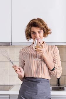 Porträt einer jungen frau, die in der hand hält, wischen den wein trinkend