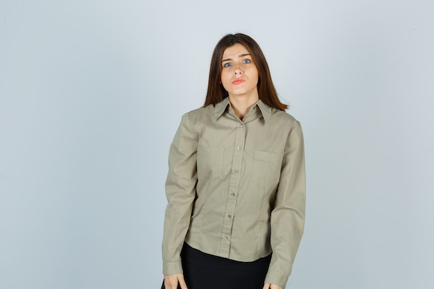 Porträt einer jungen frau, die in die kamera schaut, während sie die lippen in hemd, rock und verwirrter vorderansicht biegt