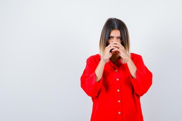 Porträt einer jungen frau, die in einem roten übergroßen hemd verschränkte hände auf der nase hält und eine süße vorderansicht sieht