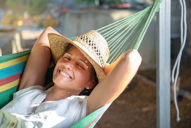 Porträt einer jungen frau, die in einer hängematte mit strohhut-sommerbild der entspannung und der freude liegt