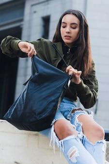 Porträt einer jungen frau, die in ihrer tasche schaut
