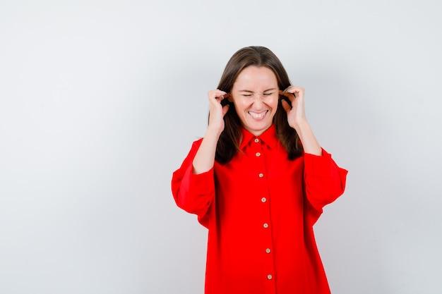 Porträt einer jungen frau, die in roter bluse die ohren mit den fingern verstopft und verärgerte vorderansicht schaut