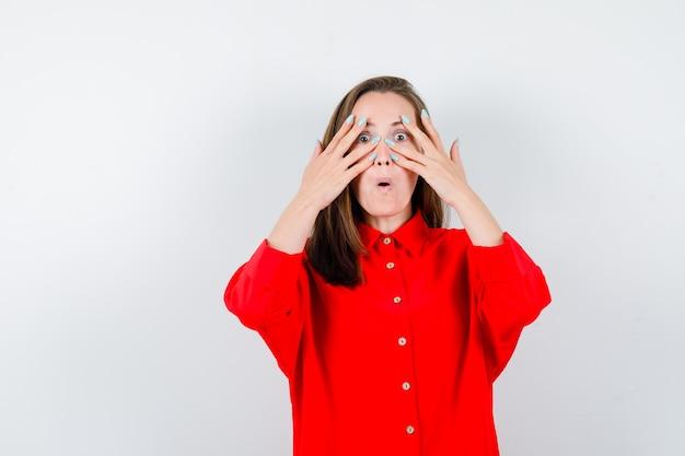 Porträt einer jungen frau, die in roter bluse durch die finger schaut und sich wunderte vorderansicht