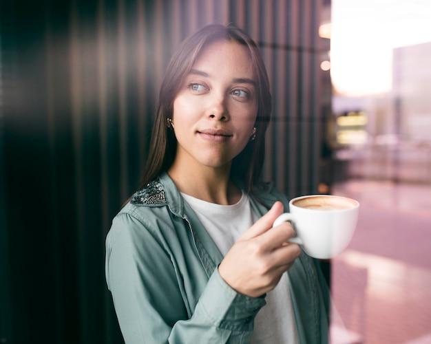 Porträt einer jungen frau, die kaffee genießt