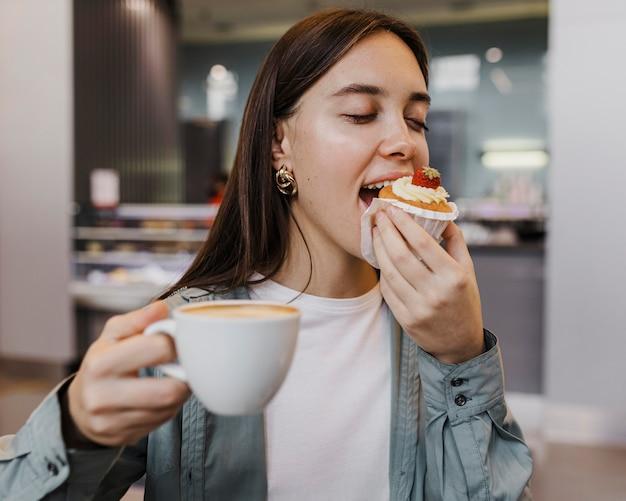 Porträt einer jungen frau, die kaffee und kuchen genießt