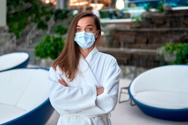 Porträt einer jungen frau, die medizinische gesichtsmaske und einen weißen bademantel trägt, während in einem wellness-spa-resort während der covid-quarantäne entspannen. neues realitätskonzept