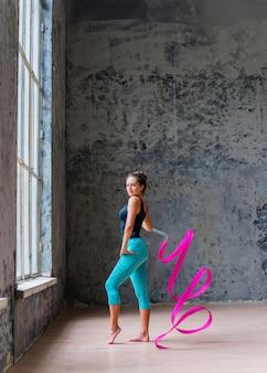 Porträt einer jungen frau, die mit rosafarbenem band tanzt