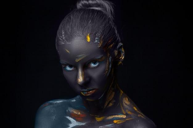 Porträt einer jungen frau, die mit schwarzer farbe bedeckt posiert