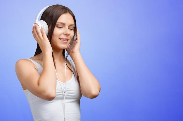 Porträt einer jungen frau, die musik mit kopfhörern hört
