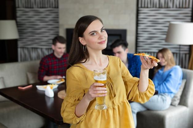 Porträt einer jungen frau, die pizza und bier in einer kneipe hält
