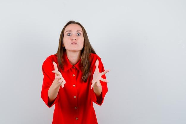 Porträt einer jungen frau, die sich vorne in roter bluse die hände ausstreckt und aggressive vorderansicht sieht