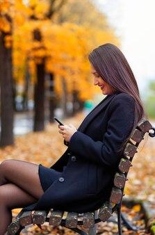 Porträt einer jungen frau, die smartphone im herbstpark verwendet