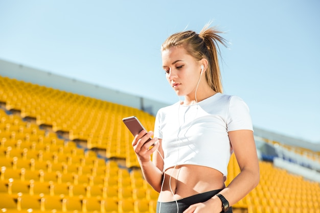 Porträt einer jungen frau, die smartphone mit kopfhörern auf freiluftstadion verwendet