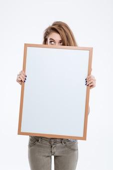 Porträt einer jungen frau, die über ein leeres brett lugt, isoliert auf weißem hintergrund