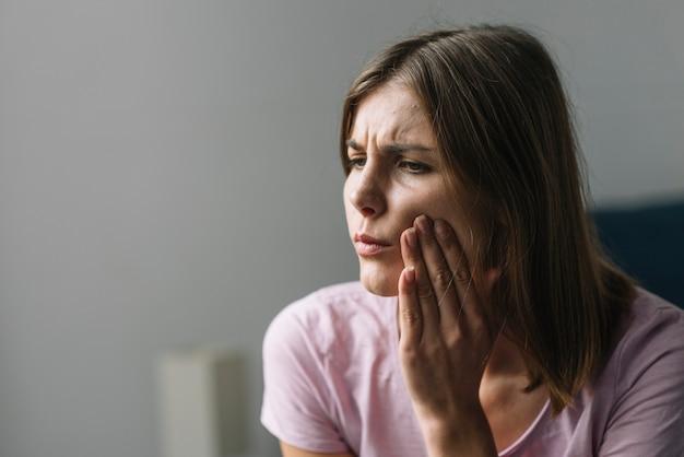 Porträt einer jungen frau, die unter nackenschmerzen leidet