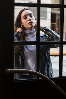 Porträt einer jungen frau, die vor geschlossener glastür steht