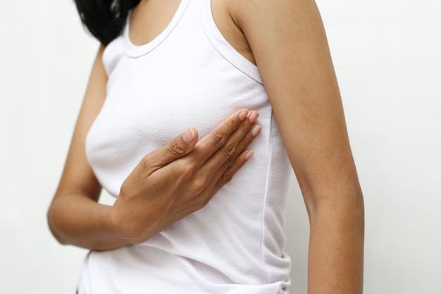 Porträt einer jungen frau, die vor schmerz ihre brust berührt