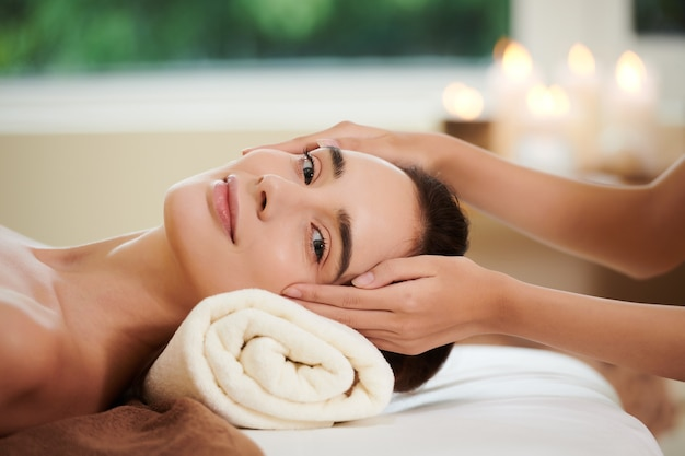Porträt einer jungen frau, die während der massage in die kamera schaut