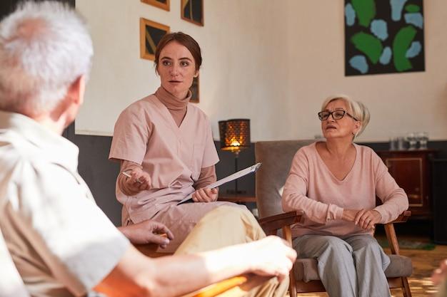 Porträt einer jungen frau, die während der therapiesitzung mit älteren menschen im altersheim spricht