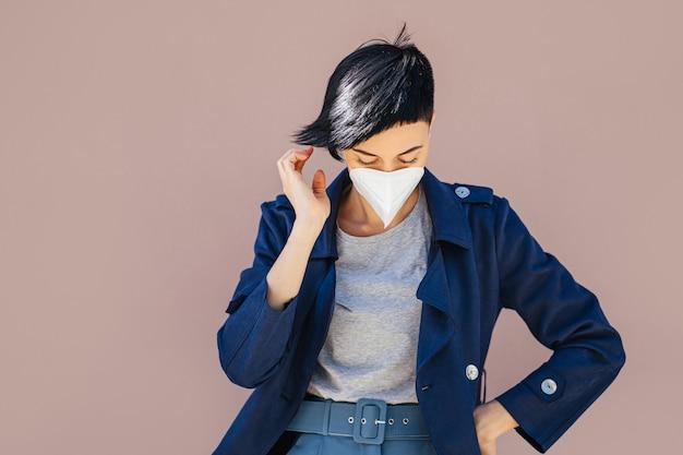 Porträt einer jungen frau, die während des ausbruchs von covid 19 eine medizinische maske auf der straße trägt. schutz in der prävention des coronavirus.