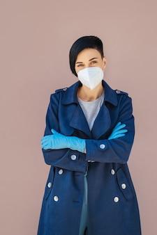 Porträt einer jungen frau, die während des ausbruchs von covid 19 eine medizinische maske und handschuhe auf der straße trägt. schutz in der prävention des coronavirus.