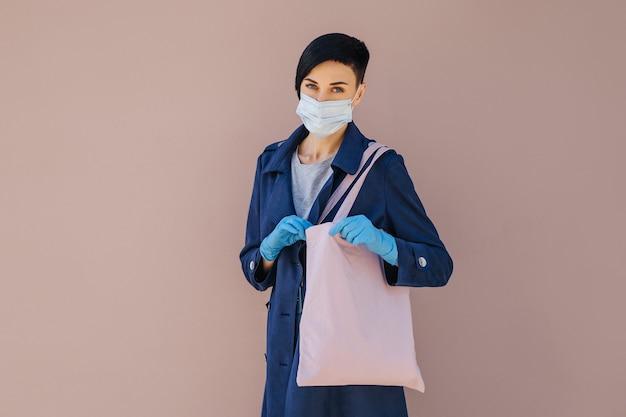 Porträt einer jungen frau, die während des ausbruchs von covid 19 medizinische maske und handschuhe mit einkaufstasche auf der straße trägt. schutz in der prävention des coronavirus.