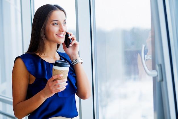 Porträt einer jungen frau gekleidet im blauen t-shirt und im schwarzen rock.