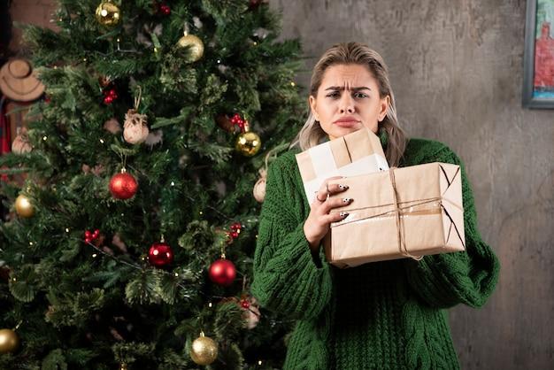 Porträt einer jungen frau im grünen pullover, der stapel von geschenkboxen hält und kamera betrachtet