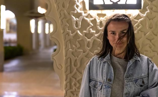 Porträt einer jungen frau im lässigen stil in einer jeansjacke im innenbereich.